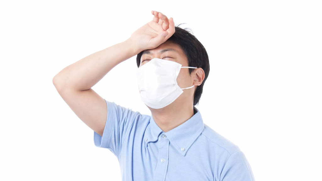 風邪をひいてマスクをしている暑そうな男性