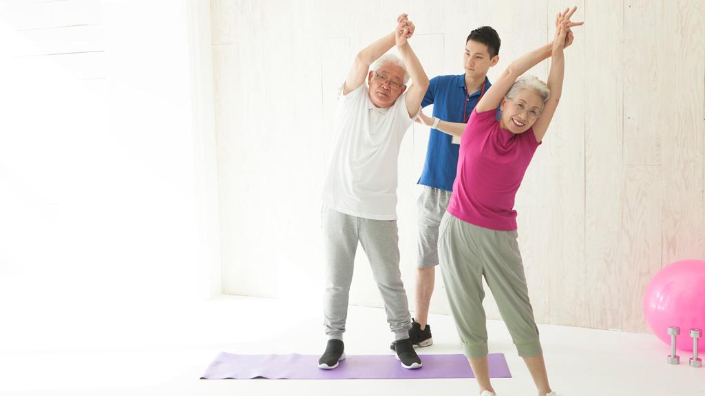 若いスタッフ指導のもと楽しく体操をする老人2人