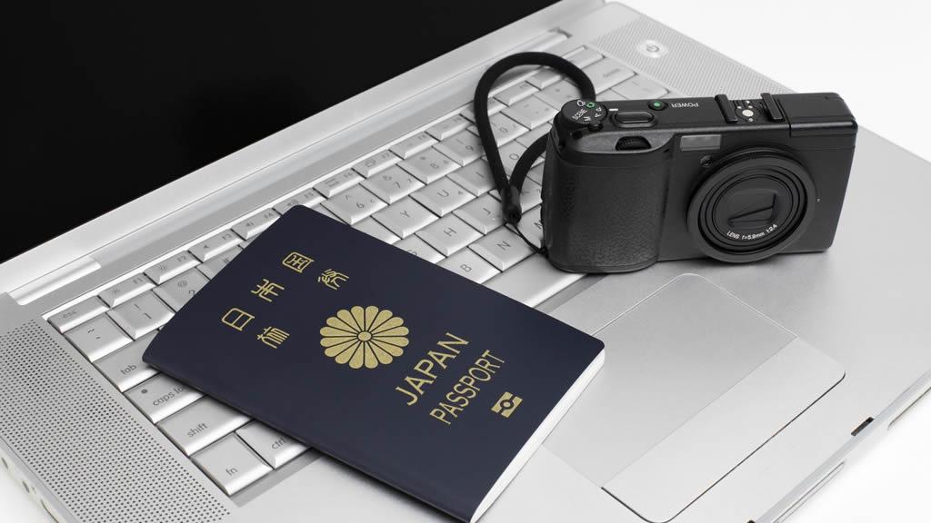 ノートPCのキーボードにのるパスポートとカメラ